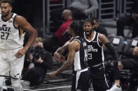 Los Angeles Clippers guard Terance Mann, center, celebrates with guard Paul George, right, after scoring and drawing a foul as Utah Jazz center Rudy Gobert stands by during the first half in Game 6 of a second-round NBA basketball playoff series Friday, June 18, 2021, in Los Angeles. (AP Photo/Mark J. Terrill)