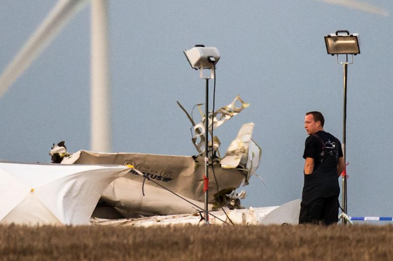 A rescue worker stands next to the debris of a small plane which crashed in a field in Marchovelette, Belgium on Saturday, Oct. 19, 2013. A plane carrying parachutists for a skydiving trip crashed in southern Belgium on Saturday, killing all 11 people aboard, officials said. A dozen minutes after the aircraft took off from a small airfield close to Namur, witnesses suddenly saw the plane go into a nosedive, lose height very quickly, then crash in a field near Fernelmont town, said its mayor, Jean-Claude Nihoul. (AP Photo/Geert Vanden Wijngaert)