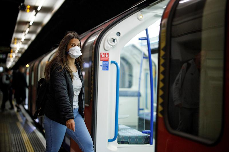 Commuters wear PPE (personal protective equipment), including a face mask as a precautionary measure against COVID-19, travel on a TfL (Transport for London) victoria line underground train towards central London from Walthamstow Central station in east London on May 18, 2020. - Britain on Sunday reported 170 more coronavirus deaths -- its lowest number since late March, when lockdown restrictions were introduced, although the figures from Northern Ireland were not included. Prime Minister Boris Johnson meanwhile acknowledged public frustration with the restrictions imposed to fight the virus. (Photo by Tolga AKMEN / AFP) (Photo by TOLGA AKMEN/AFP via Getty Images)