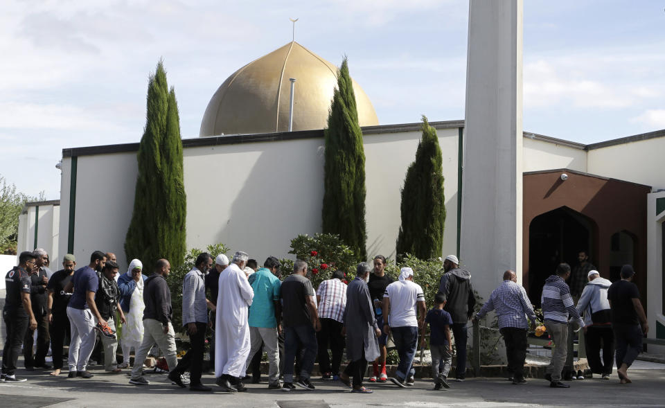 FILE - In this March 23, 2019 file photo, worshippers prepare to enter the Al Noor mosque following the previous week's mass shooting in Christchurch, New Zealand. A comprehensive report released Tuesday, Dec. 8, 2020 into the 2019 Christchurch mosque shootings in which 51 Muslim worshippers were slaughtered sheds new light on how the gunman was able to elude detection by authorities as he planned out his attack. (AP Photo/Mark Baker, File)