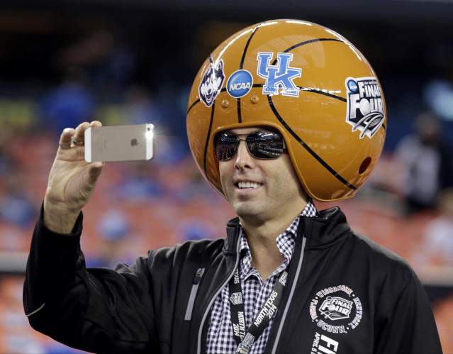 A basketball fan takes a picture before the NCAA Final Four tournament college basketball championship game between Connecticut and Kentucky Monday, April 7, 2014, in Arlington, Texas. (AP Photo/David J. Phillip)