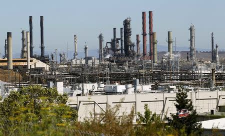 Chevron Corp's refinery, struck by a major fire, is shown still smouldering in Richmond, California, U.S. on August 7, 2012.  REUTERS/Robert Galbraith/File Photo