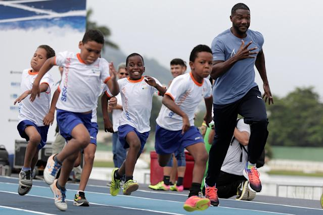 "Justin Gatlin of the U.S. runs with children from the Mangueira slum ahead of the ""Mano a Mano"" challenge, a 100-meter race, at the Brazilian Jockey Club in Rio de Janeiro, Brazil, September 29, 2017. REUTERS/Bruno Kelly"