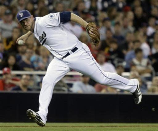 San Diego Padres third baseman Chase Headley makes a barehanded pickup on a slow roller hit by Philadelphia Phillies' Carlos Ruiz in the fifth inning of a baseball game in San Diego, Monday, June 24, 2013. Headley could not make the throw and Ruiz was safe. (AP Photo/Lenny Ignelzi)