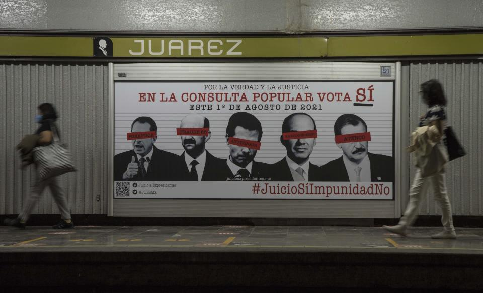 Commuters walk past an advertisement showing images of several Mexican former presidents, obscuring their eyes with red bars, and calling for citizens to participate in a referendum on whether ex-presidents should be tried for their alleged crimes during their time in office, in Mexico City, Saturday, July 31, 2021. The yes-or-no referendum on Sunday is going to cost Mexico about $25 million, and the vote is being held in the middle of a third wave of the coronavirus pandemic. (AP Photo/Christian Palma)