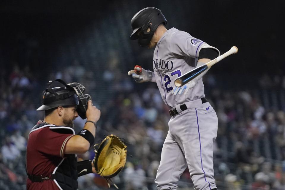 Colorado Rockies' Trevor Story, right, jumps in reaction to being hit by a pitch as Arizona Diamondbacks catcher Stephen Vogt, left, looks on during the eighth inning of a baseball game Sunday, May 2, 2021, in Phoenix. (AP Photo/Ross D. Franklin)
