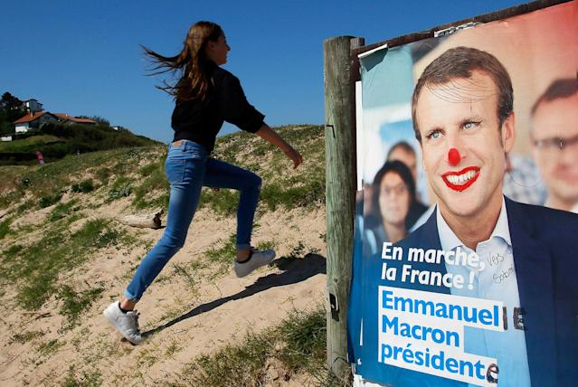 <p>A girl climbs up a dune by a defaced election campaign poster for French centrist presidential candidate Emmanuel Macron in Bidart, southwestern France, Friday, April 28, 2017. Macron will face far-right candidate Marine Le Pen in the second-round vote on May 7. (AP Photo/Bob Edme) </p>