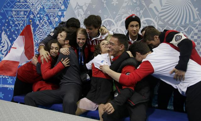 "Meagan Duhamel and Eric Radford of Canada are hugged by their team in the ""kiss and cry"" area during the Team Pairs Short Program at the Sochi 2014 Winter Olympics, February 6, 2014. REUTERS/Darron Cummings/Pool (RUSSIA - Tags: SPORT FIGURE SKATING OLYMPICS)"