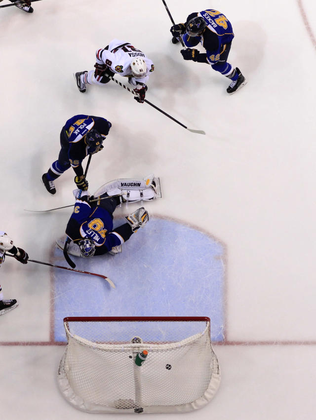 Chicago Blackhawks' Marian Hossa, top left, of Slovakia, scores past St. Louis Blues goalie Ryan Miller, bottom, Roman Polak, of the Czech Republic, and David Backes, top right, during the first period in Game 5 of a first-round NHL hockey playoff series Friday, April 25, 2014, in St. Louis. (AP Photo/Jeff Roberson)