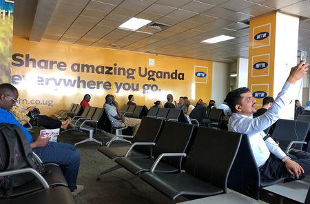 Passengers use their mobile phones at the departure lounge of the Entebbe international airport in Entebbe