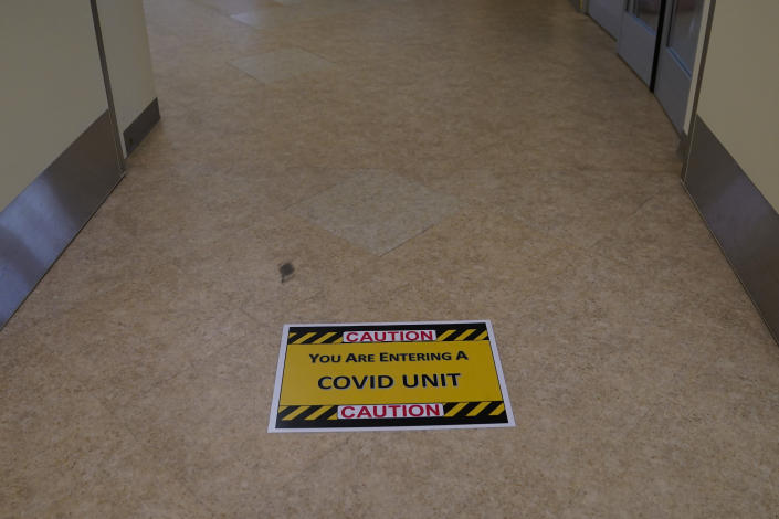 A caution sign is placed on the floor of a COVID-19 unit at St. Joseph Hospital in Orange, Calif., Thursday, Jan. 7, 2021. (AP Photo/Jae C. Hong)