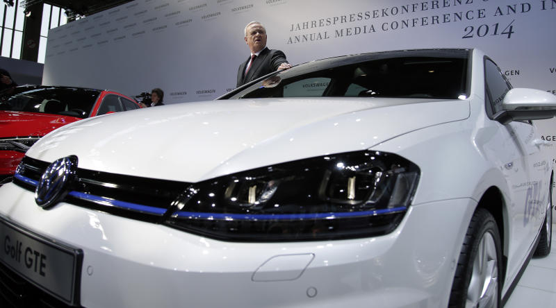 Volkswagen CEO Martin Winterkorn poses for the media next to a Golf 7 car prior to the company's annual press conference in Berlin, Germany, Thursday, March 13, 2014. German automaker Volkswagen is raising its dividend after turbocharged earnings from its Porsche luxury line outweighed slipping revenues from mass-market cars. (AP Photo/Michael Sohn)