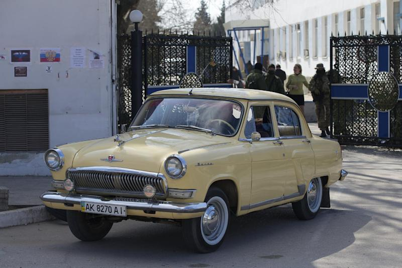 A vintage Soviet-made Volga car leaves the Ukrainian navy headquarters, which was taken under pro-Russian control Wednesday, in Sevastopol, Crimea, on Thursday, March 20, 2014. Pro-Russian forces seized three Ukrainian warships Thursday and Ukraine said its troops were being threatened in Crimea as the U.S. announced a new round of sanctions against Russia for its annexation of the Black Sea peninsula. (AP Photo/Ivan Sekretarev)