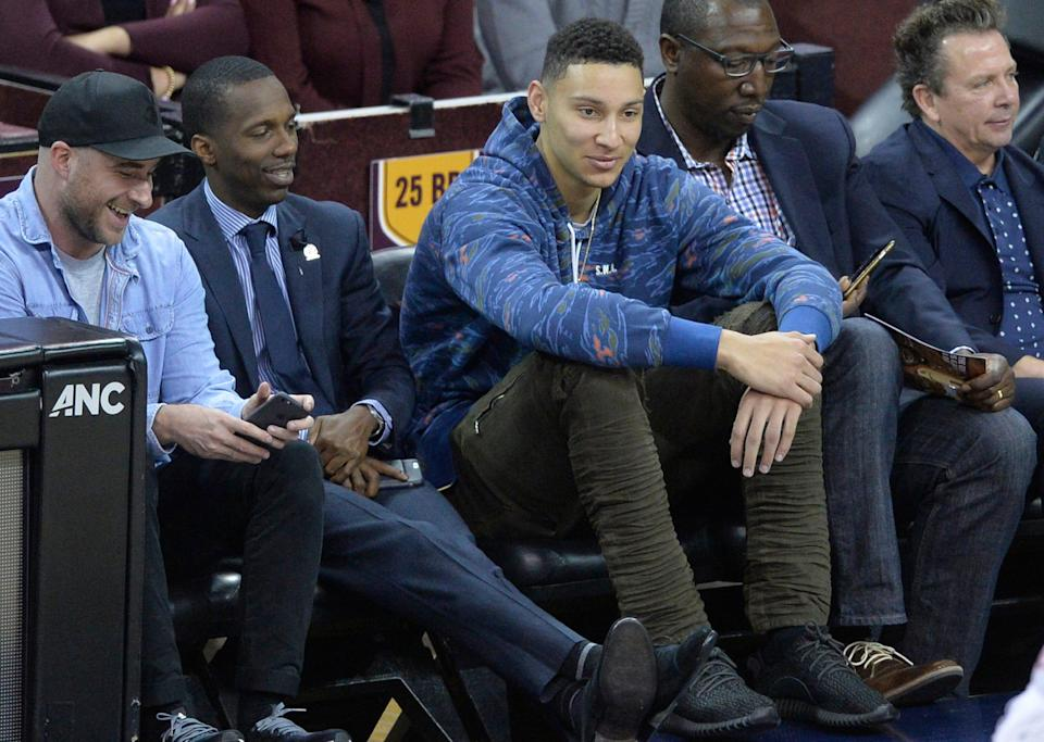 In this 2016 file photo, Ben Simmons (center) sits courtside at a Cavs game next to agent Rich Paul (left).