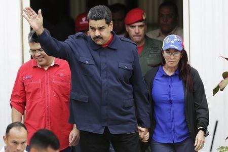 Venezuela's President Nicolas Maduro (C) greets supporters as he arrives to a rally against the opposition's law granting titles of property to beneficiaries of Mission Housing, a low-income social housing project, next to his wife and deputy of Venezuela's United Socialist Party (PSUV) Cilia Flores (R), in Caracas April 14, 2016. REUTERS/Marco Bello