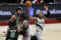 Portland Trail Blazers guard Damian Lillard, right, passes the ball over Boston Celtics guard Kemba Walker, left, during the second half of an NBA basketball game in Portland, Ore., Tuesday, April 13, 2021. (AP Photo/Steve Dykes)