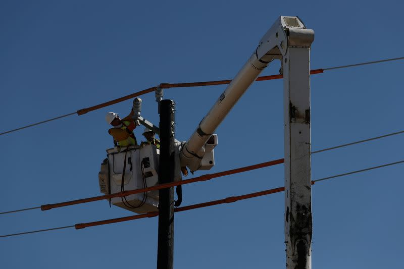 FILE PHOTO: Workers install a utility pole to support power lines after an unprecedented winter storm in Houston, Texas