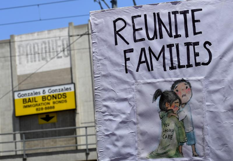 Signs are displayed during march and rally against the separation of immigrant families June 30, 2018 outside the detention facility of the US Immigration and Customs Enforcement (ICE) in Los Angeles, California. - Thousands of demonstrators, baking in the heat and opposed to the US immigration policy, marched across the country Saturday, June 30, 2018 to protest the separation of families under President Donald Trump's hardline agenda. (Photo by Mark RALSTON / AFP) (Photo credit should read MARK RALSTON/AFP/Getty Images)