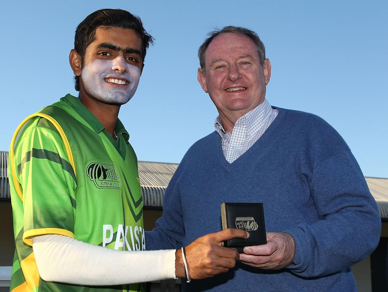 SUNSHINE COAST, AUSTRALIA - AUGUST 11:  Muhammad Babar Azam of Pakistan (L) is presented with the Man of the Match award following the ICC U19 Cricket World Cup 2012 match between Pakistan and Afghanistan at John Blanck Oval on August 11, 2012 in Sunshine Coast, Australia.  (Photo by Graham Denholm-ICC/Getty Images)
