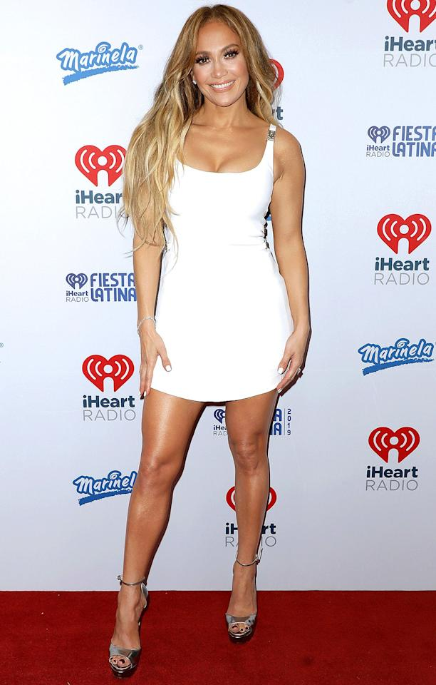 in a white curve-hugging mini dress with buckled straps and metallic platform pumps at 2019 iHeartRadio Fiesta Latina in Miami.