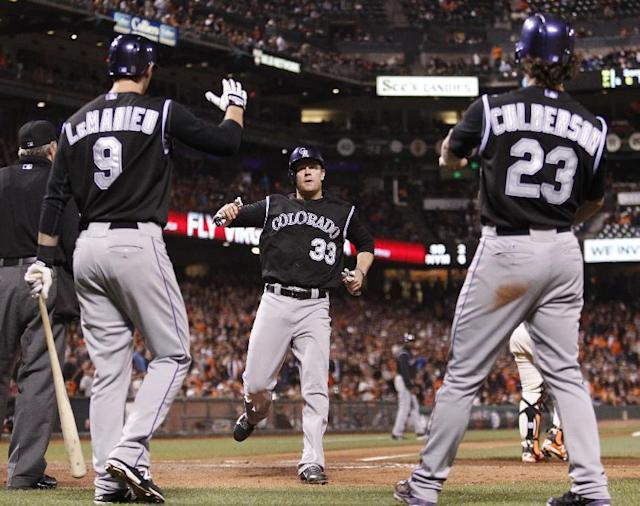 Colorado Rockies' Justin Morneau, center, is congratulated by Charlie Culberson, right, and DJ LeMahieu after Morneau and Culberson scored on a two RBI single by Ryan Wheeler during the ninth inning of a baseball game against the San Francisco Giants in San Francisco, Friday, June 13, 2014. (AP Photo/Beck Diefenbach)