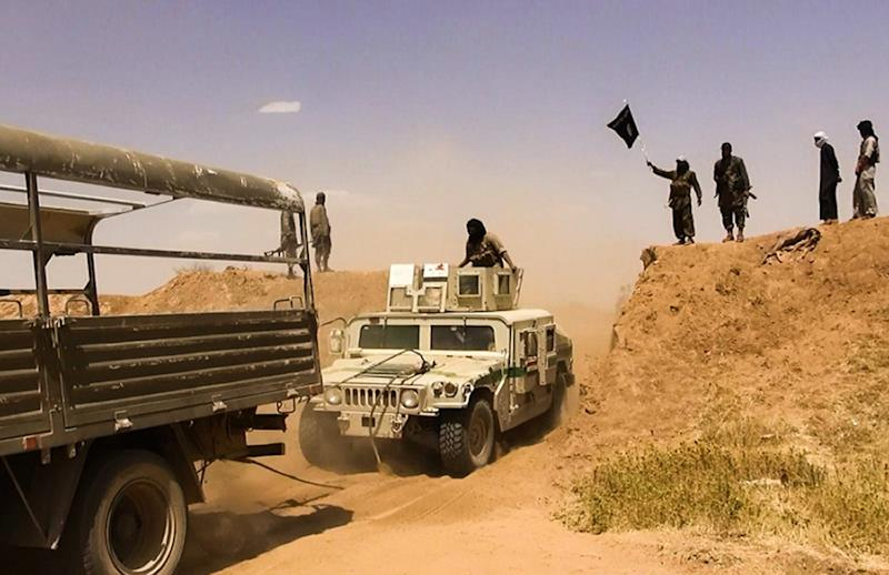 An image made available by the jihadist Twitter account Al-Baraka News on June 9, 2014 allegedly shows Islamic State militants waving the trademark jihadits flag as vehicles drive on a newly cut road through the Syrian-Iraqi border