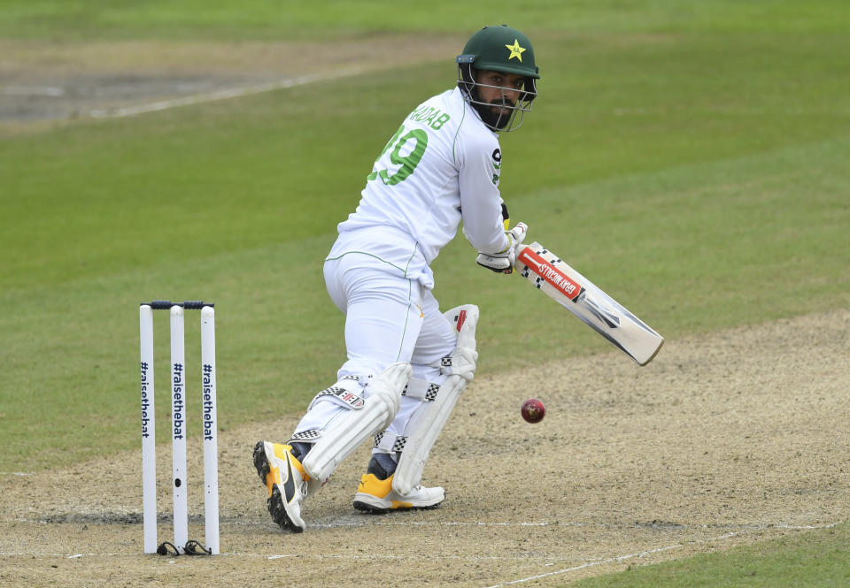 Pakistan's Shadab Khan watches the ball after playing a shot during the second day of the first cricket Test match between England and Pakistan at Old Trafford in Manchester, England, Thursday, Aug. 6, 2020. (Dan Mullan/Pool via AP)