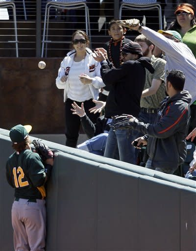 Oakland Athletics right fielder Collin Cowgill (12) looks on as fans in right field miss a foul ball hit by San Francisco Giants designated hitter Hector Sanchez during the second inning of an exhibition baseball game in San Francisco, Wednesday, April 4, 2012. (AP Photo/Eric Risberg)