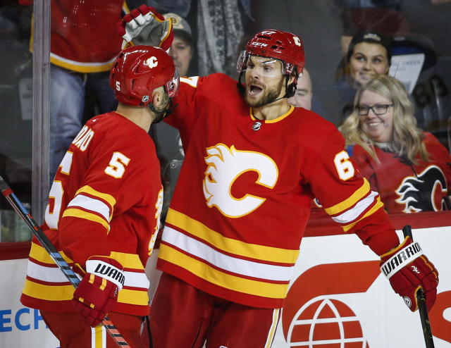 Calgary Flames' Michael Frolik, right, of the Czech Republic, celebrates his second goal with teammate Mark Giordano during NHL hockey action against the Boston Bruins in Calgary, Alberta, Wednesday, Oct. 17, 2018. (Jeff McIntosh/The Canadian Press via AP)