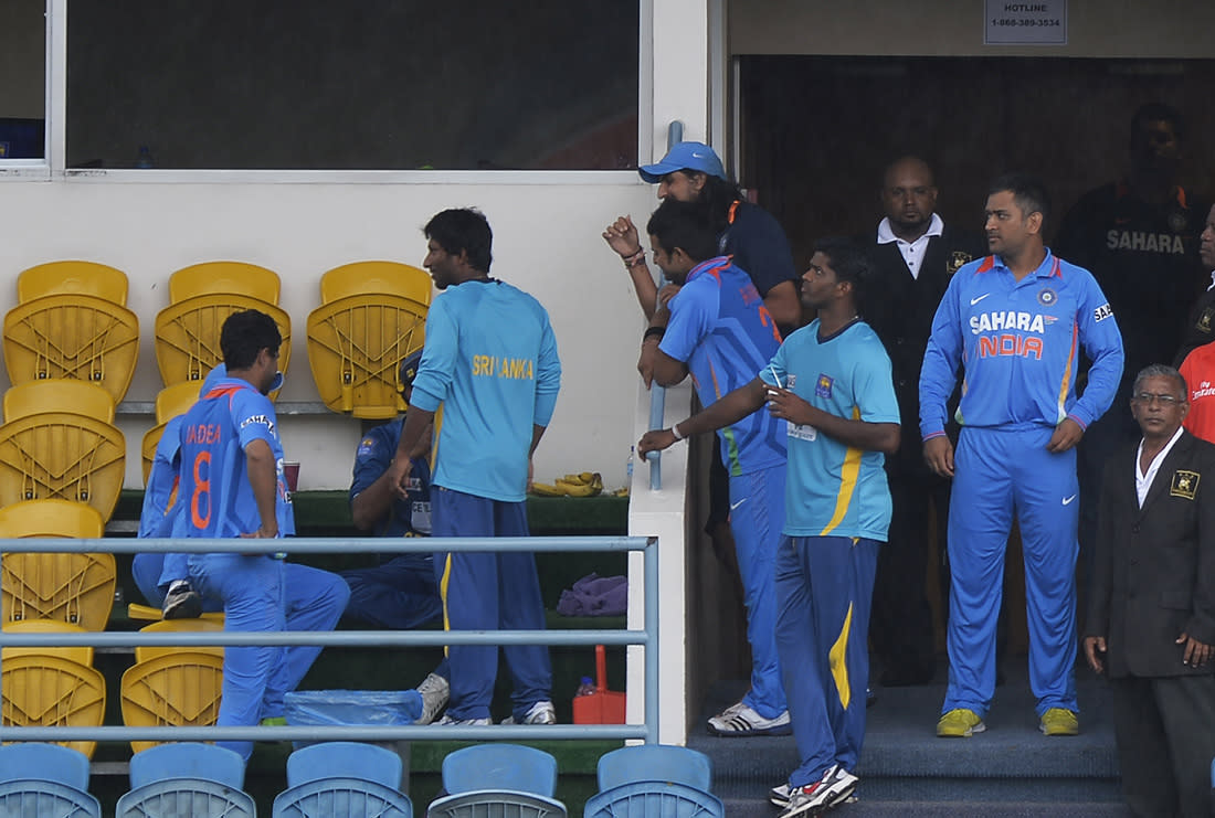 Indian and Sri Lanka cricketers chat as rain interrupts the sixth match of the Tri-Nation series between India and Sri Lanka at the Queen's Park Oval stadium in Port of Spain on July 9, 2013. The match is at halt due to rain. AFP PHOTO/Jewel Samad