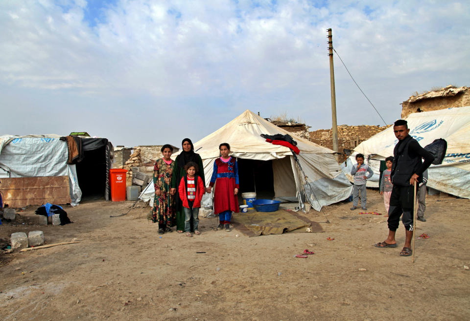 Fatima Hamed, second left, and her family stand outside their tent that she brought from the Hamam Alil camp for displaced people in Ninevah following a government-ordered closure, in the village of Debaja, west of Mosul, Iraq, Nov. 29, 2020. A push by the Iraqi government to close displacement camps by the end of the year threatens to leave tens of thousands of people homeless and without aid during a pandemic and at the onset of winter. (AP Photo/Samya Kullab)