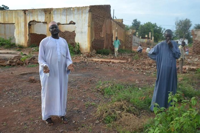 Ali Mahamat (L) stands next to the ruins of his shop in Boda, southern Central African Republic, on May 21, 2015 (AFP Photo/Patrick Fort)