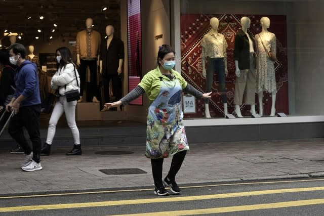 A woman wearing masks stretches her arms in Hong Kong
