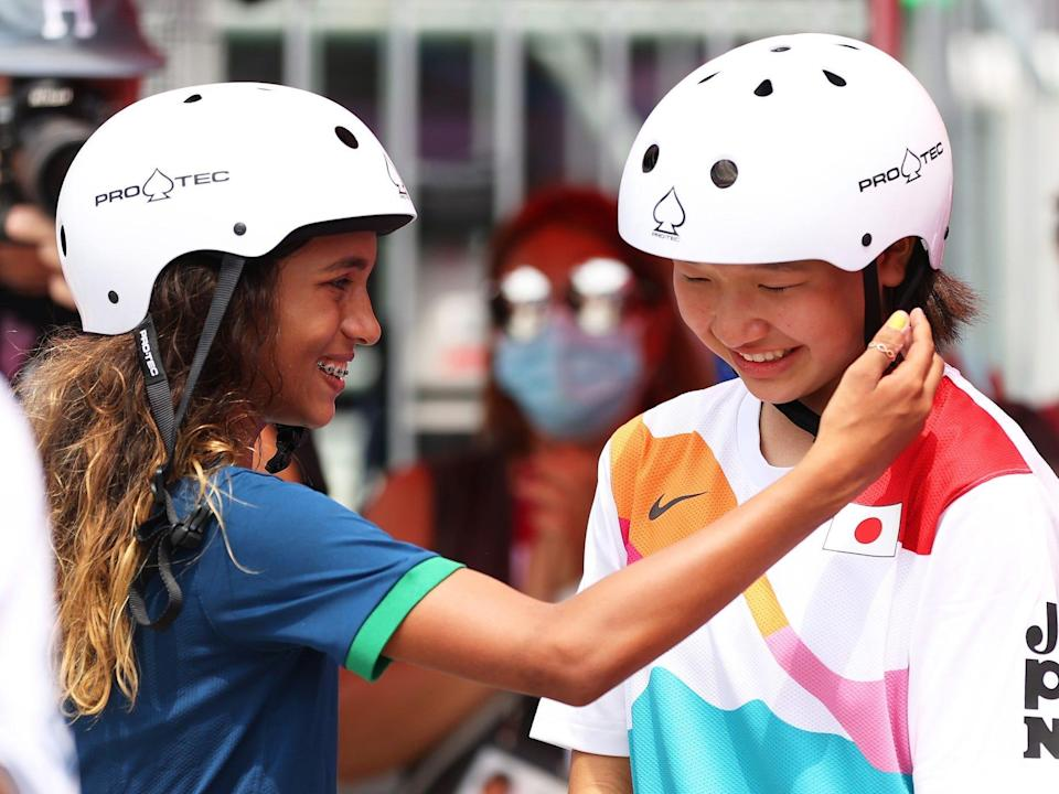 Rayssa Leal of Team Brazil puts her hand to the face of Momiji Nishiya of Team Japan during the Tokyo Olympic street skating competition.