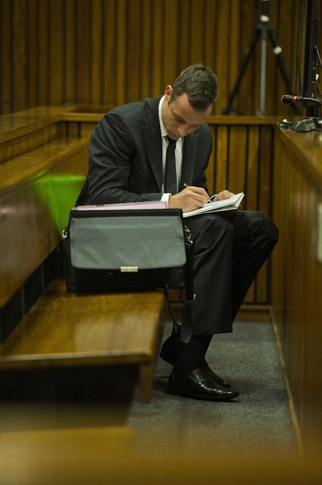 Oscar Pistorius makes notes as he sits in the dock during his trial in court in Pretoria, South Africa, Thursday, March 13, 2014. Pistorius is charged with the shooting death of his girlfriend Reeva Steenkamp, on Valentines Day in 2013. (AP Photo/Alet Pretorius, Pool)