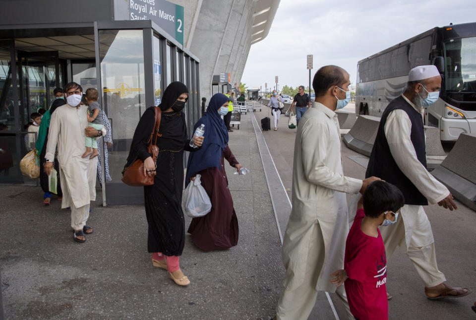 FILE - In this Tuesday, Aug. 31, 2021, file photo, families evacuated from Kabul, Afghanistan, walk to board a bus after they arrived at Washington Dulles International Airport, in Chantilly, Va. U.S. religious groups of many faiths are gearing up to assist the thousands of incoming refugees. (AP Photo/Gemunu Amarasinghe, File)