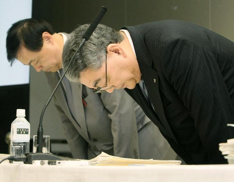 Tokyo Electric Power Company president Toshio Nishizawa (R) bows to apologize to victims of the nuclear accident at the Fukushima power plant during a press conference to announce the company's financial results in Tokyo on November 4, 2011