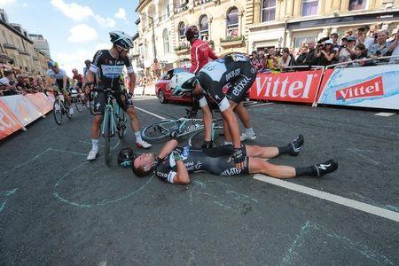 Omega Pharma-Quick Step team rider Cavendish of Britain gets assistance after crashing during a mass sprint next to the finish line of the first 190.5 km stage of the Tour de France