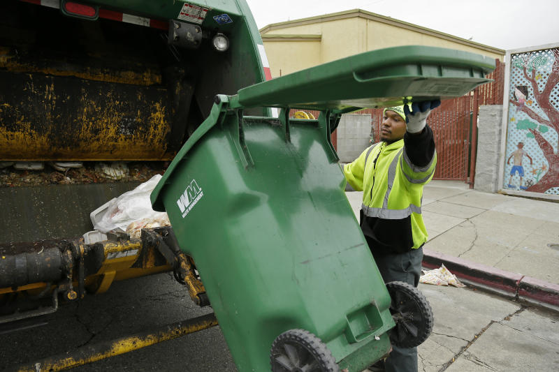 In this photo taken Thursday, Oct. 27, 2016, apprentice garbage man Corey Lever collects trash outside a school in Oakland, Calif. A new partnership between Waste Management of Alameda County Inc., the nonprofit Oakland Civicorps and unions gives young adults, often high school dropouts from low-income communities, a chance to become teamster drivers after two years of training. Like most little boys, Lever liked trucks, but his favorite was always the garbage truck. (AP Photo/Eric Risberg)