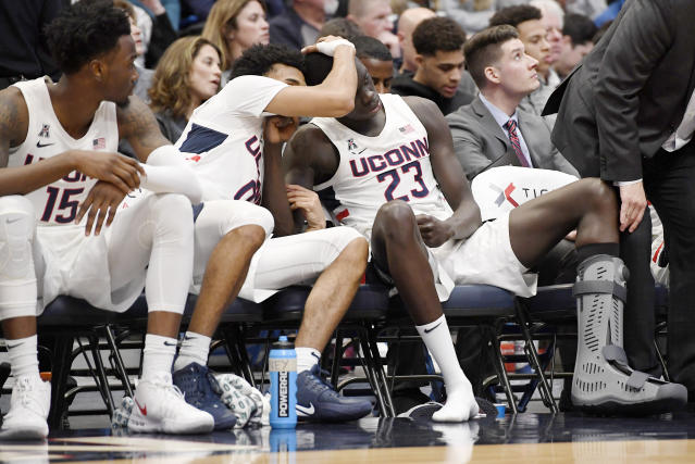 Connecticut's Akok Akok (23) is consoled by by teammate Jalen Gaffney, center, as Sidney Wilson, left, looks on, after Akok returned to the bench with a boot on his left foot in the first half of an NCAA college basketball game against Memphis, Sunday, Feb. 16, 2020, in Hartford, Conn. (AP Photo/Jessica Hill)