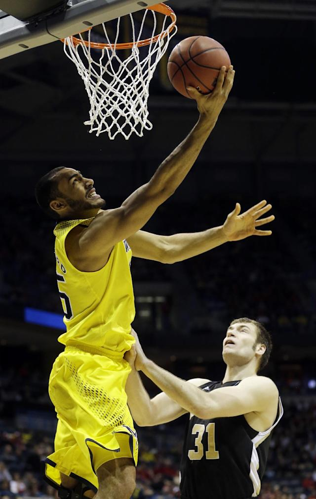 Michigan forward Jon Horford (15) goes to the basket over Wofford forward C.J. Neumann (31) during the first half of a second round NCAA college basketball tournament game Thursday, March 20, 2014, in Milwaukee. (AP Photo/Morry Gash)