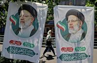 A woman walks past banners of presidential election favourite Ebrahim Raisi on the eve of polling day in Tehran