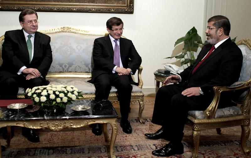 FILE - In this Monday, July 2, 2012 file photo, Turkish Ambassador to Egypt, Huseyin Avni Botsali, left, and Turkish Foreign Minister Ahmet Davutoglu, center, meet with Egyptian President Mohammed Morsi, right, at the Presidential Palace in Cairo, Egypt. Egypt downgraded diplomatic relations Saturday with Turkey and expelled its ambassador from Cairo, a sharp escalation in tensions between the two countries that mounted after a military coup ousted the country's Islamist president this summer. (AP Photo/Maya Alleruzzo, File)