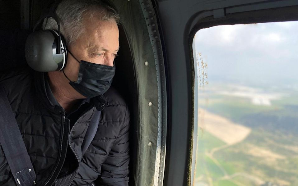 Israeli Defence Minister Benny Gantz wears a face mask as he looks out from the window of a helicopter during a tour of the Gaza border area, - Reuters/Reuters