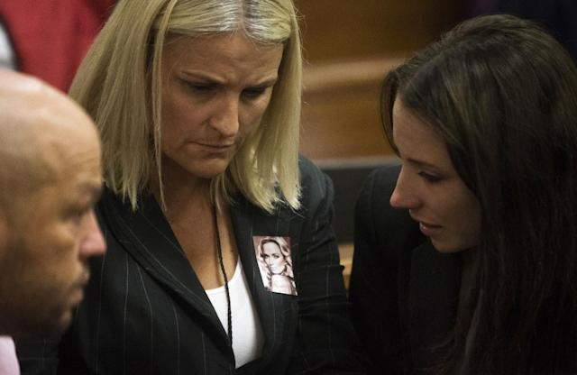 Oscar Pistorius' sister, Aimee, right, speaks with unidentified members of Reeva Steenkamp's family, one wearing a portrait Reeva, on the fourth day of Pistorius' trial at the high court in Pretoria, South Africa, Thursday, March 6, 2014. Pistorius is charged with murder for the shooting death of his girlfriend, Reeva Steenkamp, on Valentines Day in 2013. (AP Photo/Marco Longari, Pool)