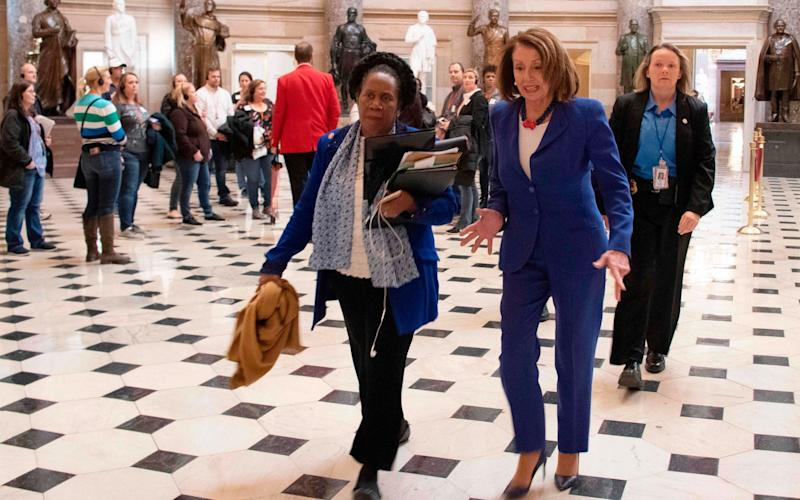 US Speaker of the House Nancy Pelosi (C R)) and congresswoman Sheila Jackson Lee (C L) walk to the House Chambers, to vote on blocking the national emergency over border situation - AFP
