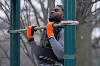 """Zay Frection works out in """"the gym"""" at Fort Greene Park, Thursday, Dec. 23, 2020, in the Brooklyn borough of New York. Frection said, """"A lot of people like the gym, which is fine. But I always find the most effective training for me is body weight training. So I go to the parks and use the pull-up bar. The pandemic has made it hard for everybody to get in shape. But with me, I can just come outside, as long as it's not raining, I can get a nice little workout, be consistent, build my body and fight off corona."""" (AP Photo/Kathy Willens)"""