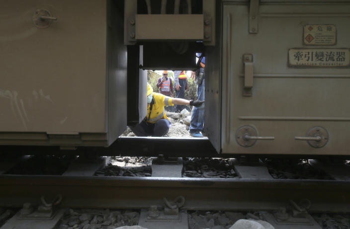 Workers examine the derailed train near Taroko Gorge in Hualien, Taiwan on Saturday, April 3, 2021. The train partially derailed in eastern Taiwan on Friday after colliding with an unmanned vehicle that had rolled down a hill, killing and injuring dozens. Workers began removing some of the train cars and repair work also has begun on the tracks including the tunnel where part of the eight-car train crashed. (AP Photo/Chiang Ying-ying)