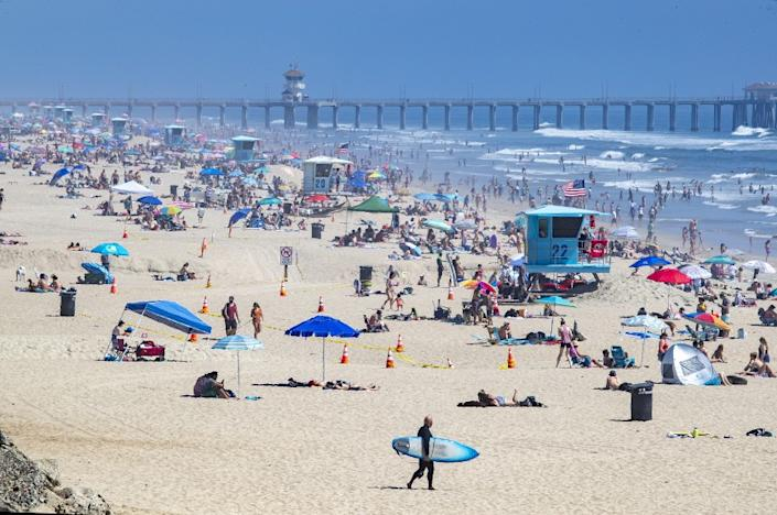 "Thousands of beachgoers enjoy a warm, sunny day in Huntington Beach on April 25 amid state-mandated stay-at-home orders designed to stave off the coronavirus pandemic. <span class=""copyright"">(Allen J. Schaben / Los Angeles Times)</span>"