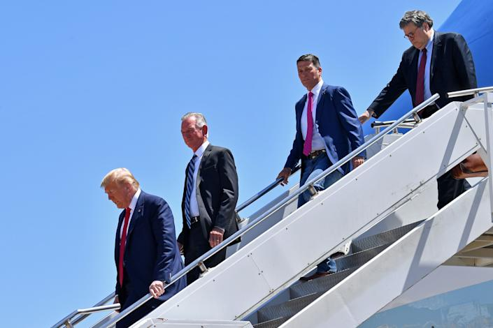 President Donald Trump steps off Air Force One, alongside Attorney General William Barr, U.S. House candidate Ronny Jackson (2nd from right), and U.S. Senate candidate Tommy Tuberville (2nd from left), upon arrival in Dallas, Texas, on June 11, 2020.
